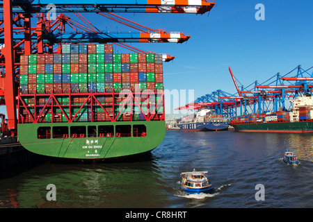 Container ship, Xin Ou Zhou, being loaded with containers at the Container Terminal Eurokai, left, and other ships - Stock Photo