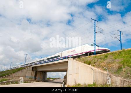 Madrid-Barcelona high-speed train traveling over a side road. La Alcarria, Guadalajara province, Castilla La Mancha, - Stock Photo