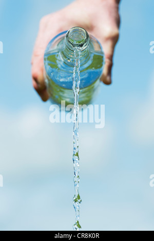 Pouring drinking water from a glass bottle against a blue sky - Stock Photo