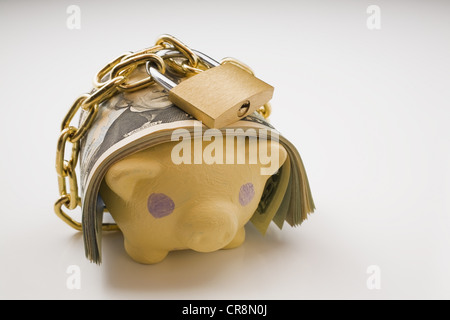 Piggy bank with bank notes and padlock
