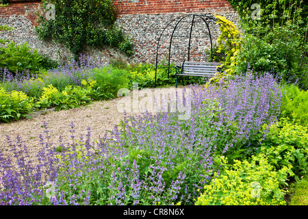 Herb Borders Lining A Gravel Path Leading To An Arbour