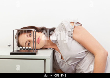 Young woman watching newtons cradle - Stock Photo