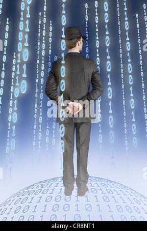 Businessman standing on binary globe with binary strings - Stock Photo