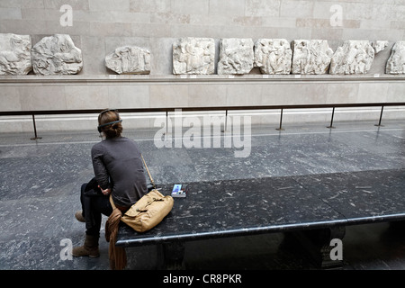 Young museum visitor with audio guide looking at the Elgin Marbles, marble reliefs from the Athens Parthenon, British - Stock Photo