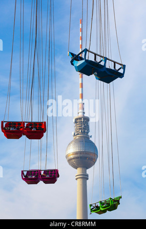 Empty seats of a Chairoplane or swing carousel in front of the Television Tower in Alexanderplatz, Berlin, Germany, - Stock Photo