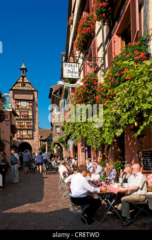 Alley with restaurant and Dolder Tower in Colmar, Alsace, France, Europe - Stock Photo