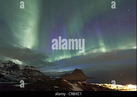 Rare purple-blue Northern Lights (Aurora borealis) above the Mt. Kirkjufell and Grundarfjoerður city, Snæfellsnes, - Stock Photo