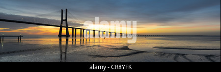 Panorama image of the Vasco da Gama bridge in Lisbon, Portugal during sunrise with reflection in the Tagus river - Stock Photo