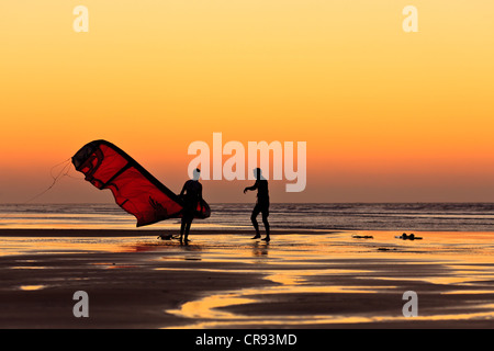 Silhouettes of two men walking on the beach with a kite surfer sail at sunset, Essaouira, Morocco, Africa - Stock Photo