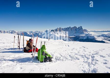Ski tourers taking a break on the summit of Mt Uribrutto, above Passo Valles, Dolomites, Pale di San Martino mountains - Stock Photo