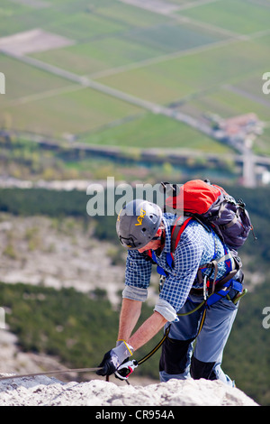 Climber climbing on the Che Guevara fixed rope route on Casale mountain in the Sarcatal valley, Lake Garda region - Stock Photo