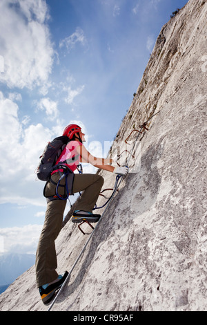 Mountaineer climbing on the Che Guevara fixed rope route on Monte Casale mountain, Sarca valley, Lake Garda region - Stock Photo