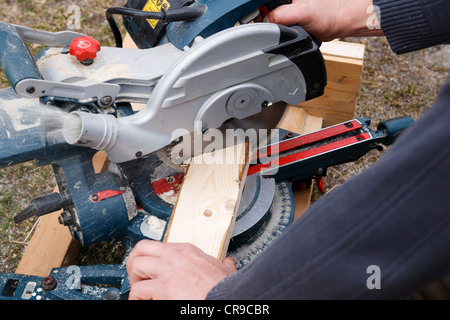 Carpenter cutting wooden plank with high speed circular saw - Stock Photo