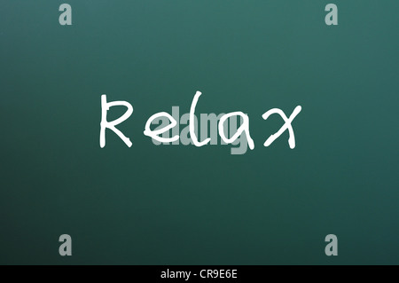 Relax written with chalk on a green chalkboard - Stock Photo