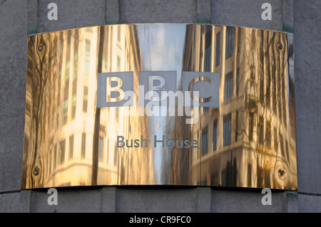 Brass BBC name plate & reflections on curved surface outside of the Bush House headquarters building for BBC World - Stock Photo