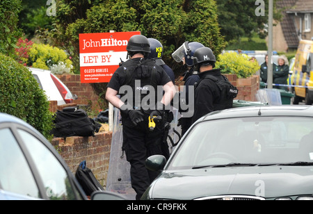 Police some of them armed surround a house in Colbourne Avenue Brighton today One officer holds a taser behind his - Stock Photo