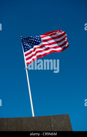 The American flag fluttering atop a flagpole - Stock Photo