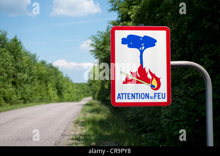 French attention au feu sign by the roadside in a woodland area - Stock Photo