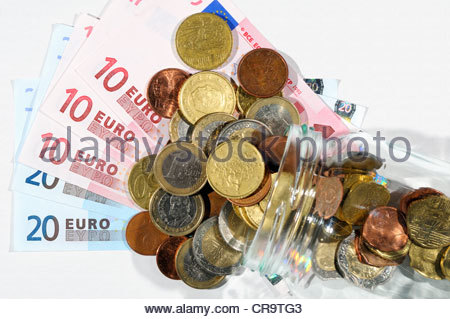 Euro notes and coins in a glass jar, England - Stock Photo