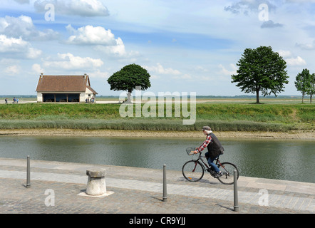 Man riding bicycle along River Somme in the baie de somme St Valery Sur Somme Picardy France - Stock Photo