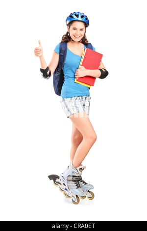 Full length portrait a girl on rollers holding notebooks and giving thumb up isolated against white background - Stock Photo