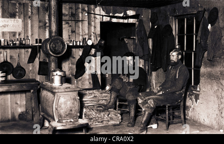 Two Men in Crude Cabin with Cat - Stock Photo