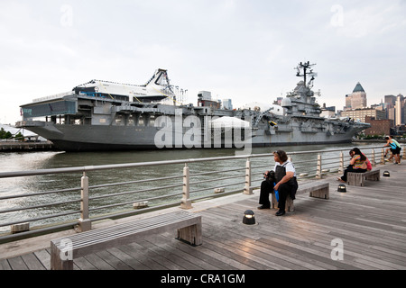 people on Hudson River Pier 84 view space shuttle Enterprise being readied for exhibit dwarfing flight deck Intrepid - Stock Photo