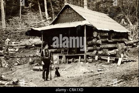 Tough Guy & Harmless Dog Guarding Crude Log Cabin - Stock Photo