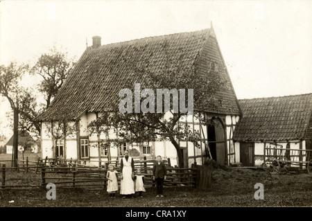 Mother & Three Children at Half-Timbered European Farmhouse - Stock Photo