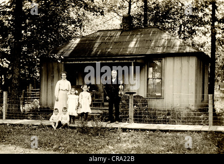 Family of Six in front of Small Cottage - Stock Photo