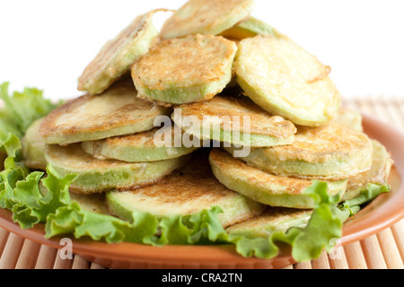 Courgettes fried in egg batter. Lot of fried zucchini on a brown dish - Stock Photo