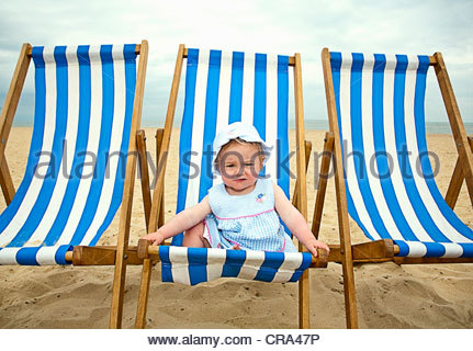 Baby sitting in lawn chair on beach - Stock Photo