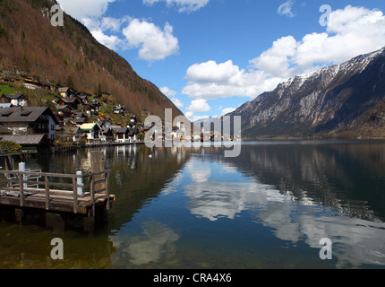 View of boat sailing and panorama of lake and Hallstatt village as a background. Hallstattersee - mountain lake - Stock Photo