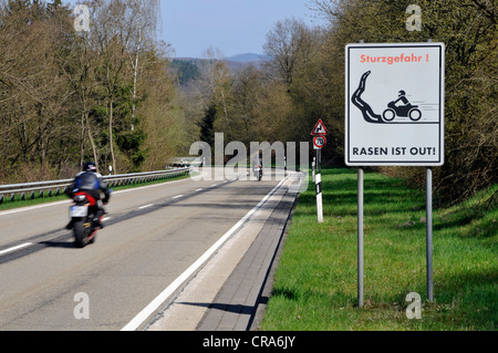 Motorcyclist on a country road with a warning sign, Sturzgefahr - Rasen ist out, German for dangerous curves - no - Stock Photo