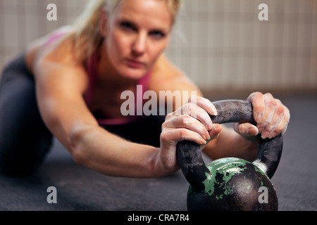 Portrait of young woman having a short break in her kettlebell crossfit workout - Stock Photo