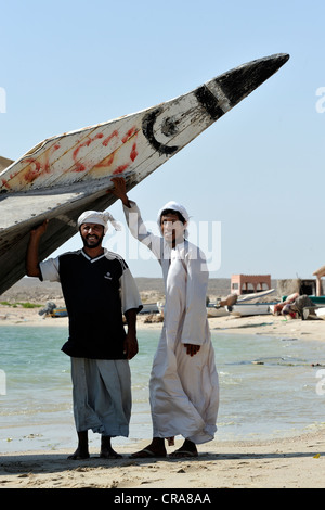 Men posing in front of their Dhow boat in Sur, Oman, Middle East - Stock Photo