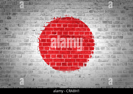 An image of the Japan flag painted on a brick wall in an urban location - Stock Photo