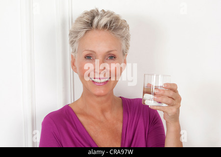 Older woman having glass of water - Stock Photo