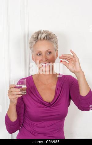 Older woman taking medication - Stock Photo
