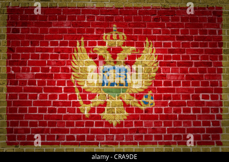 An image of the Montenegro flag painted on a brick wall in an urban location - Stock Photo