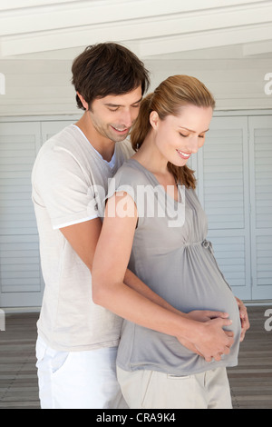 Man holding pregnant girlfriends belly - Stock Photo