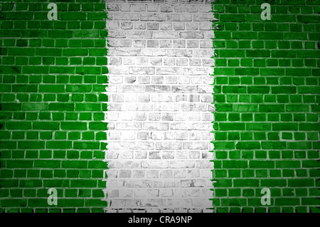 An image of the Nigeria flag painted on a brick wall in an urban location - Stock Photo