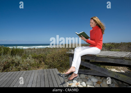 Woman reading book on wooden bench - Stock Photo