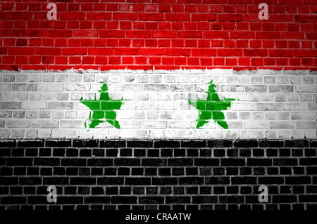 An image of the Syria flag painted on a brick wall in an urban location - Stock Photo