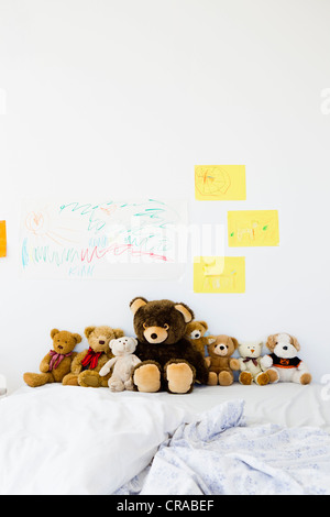Teddy bears and childs drawings on bed - Stock Photo