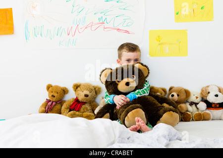 Boy hugging teddy bear on bed - Stock Photo