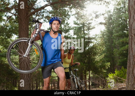 Couple carrying mountain bikes in forest - Stock Photo
