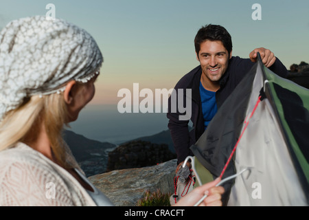 Couple setting up tent on hillside - Stock Photo