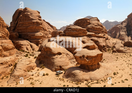 Off-road vehicle driving between rocks in the desert, Wadi Rum, Hashemite Kingdom of Jordan, Middle East, Asia - Stock Photo