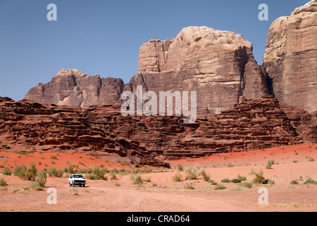 Off-road vehicle in front of mountains, vast plains and red sand in the desert, Wadi Rum, Hashemite Kingdom of Jordan - Stock Photo